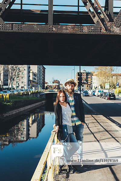 Porträt eines kühlen Paares  das sich an ein Kanalgeländer lehnt