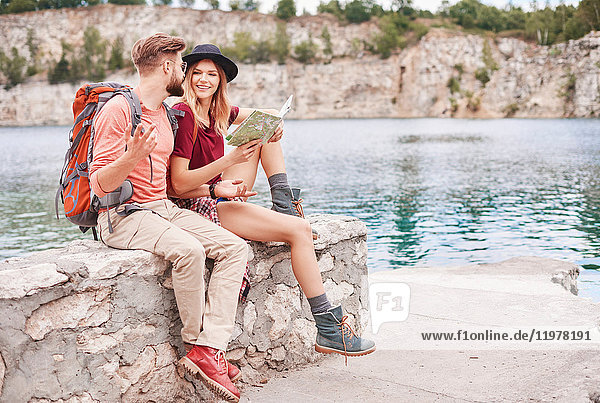 Couple sitting on wall by water looking at map  Krakow  Malopolskie  Poland  Europe