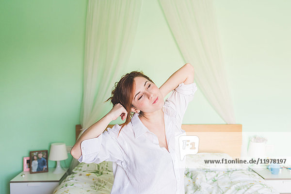 Young woman on bed yawning and stretching