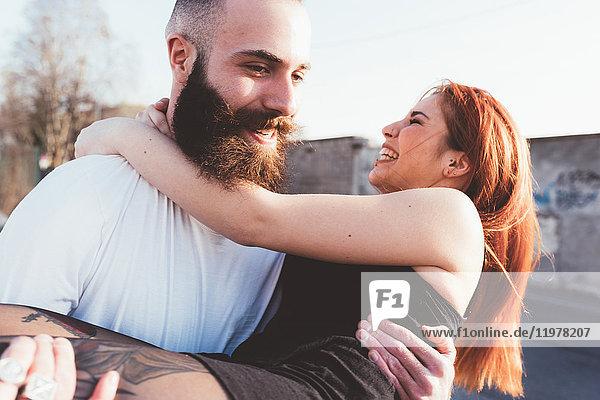 Bärtiger Mann trägt lächelnde Frau auf dem Arm