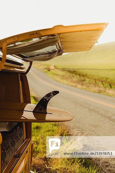 Gelbes Surfbrett im Kofferraum eines alten Wohnmobils am Straßenrand  Exeter  Kalifornien  USA