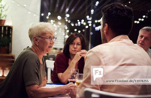 Gruppe von Personen  die am Tisch sitzen und eine Mahlzeit genießen