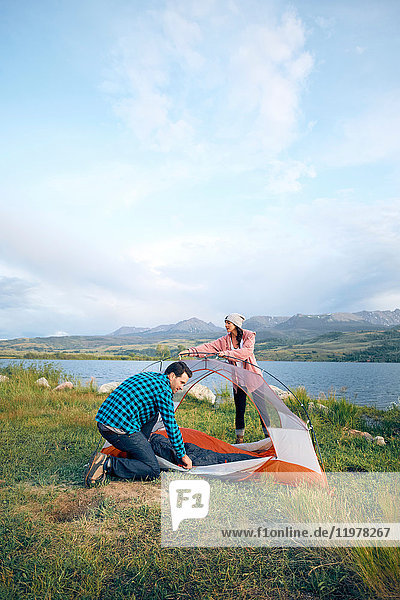 Couple in rural setting  putting up tent  Heeney  Colorado  United States