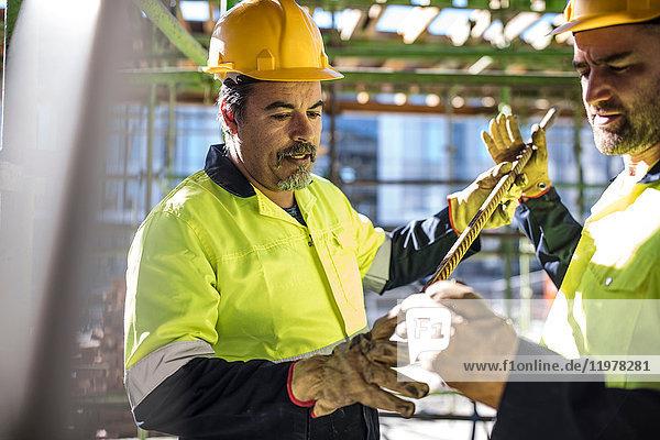 Bauarbeiter schauen auf Metallstab