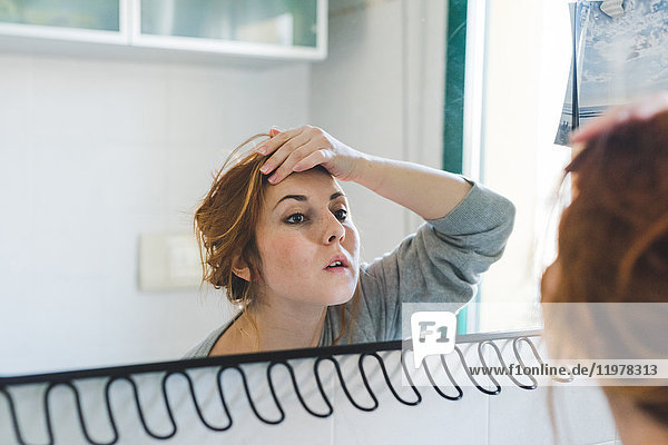 Reflection of young woman with hand on forehead looking at bathroom mirror