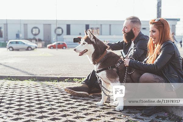 Paar sitzt mit Hund  der wegschaut