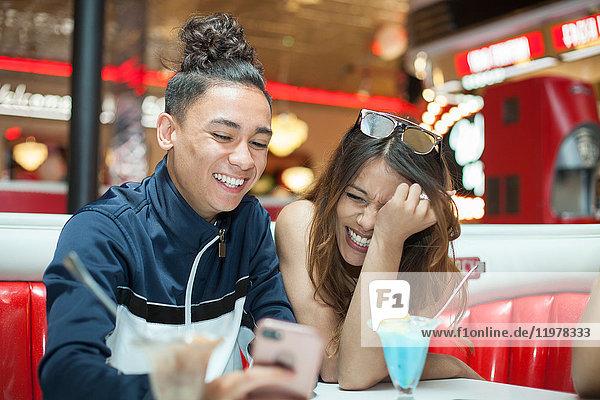 Junges Paar sitzt im Diner  schaut auf Smartphone  lacht