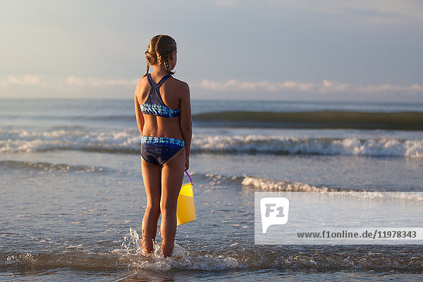 Rear view of girl on beach holding bucket  North Myrtle Beach  South Carolina  United States  North America