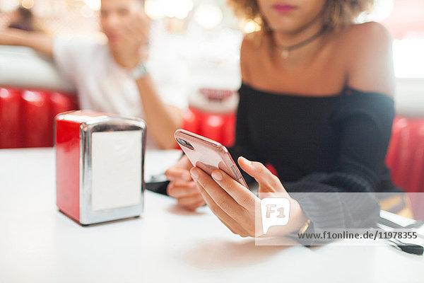 Junges Paar  im Diner sitzend  junge Frau mit Smartphone  Mittelteil  Nahaufnahme