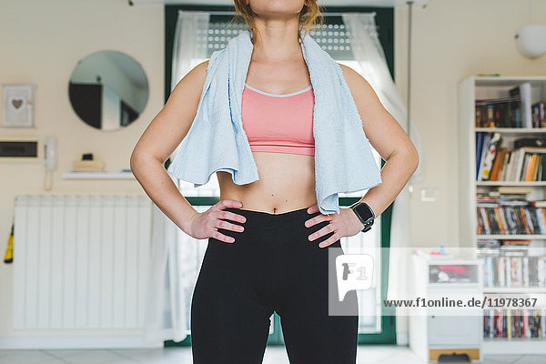 Mid section of young woman training  standing with hands on hips