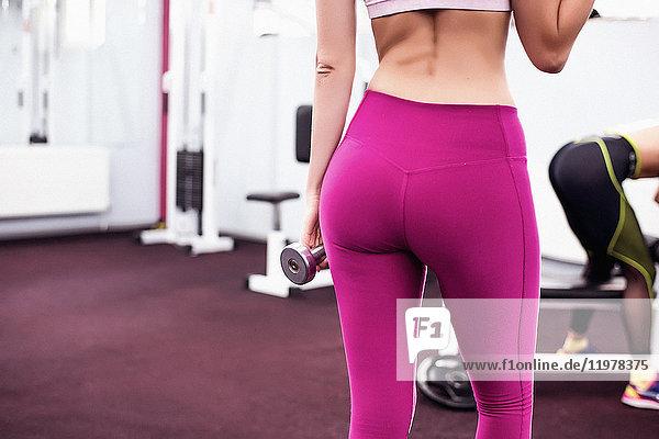 Geschnittene Rückansicht einer Frau im Fitnessstudio mit Lycra