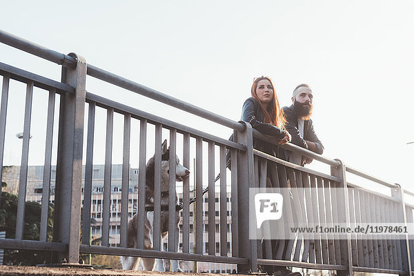 An Geländer gelehntes Paar schaut weg