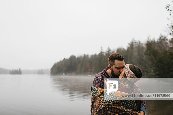 Couple by lake wrapped in blanket kissing  Bancroft  Canada  North America