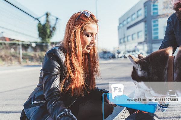 Rothaarige Frau gibt Hund Wasser zu trinken