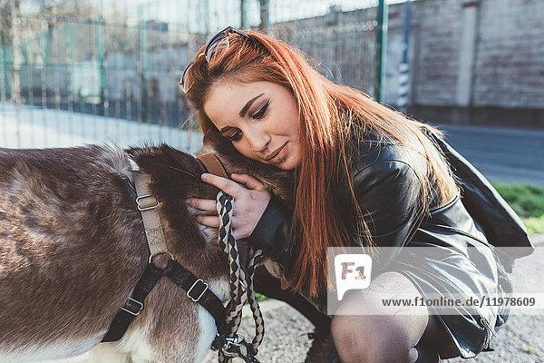 Rothaarige Frau umarmt Hund