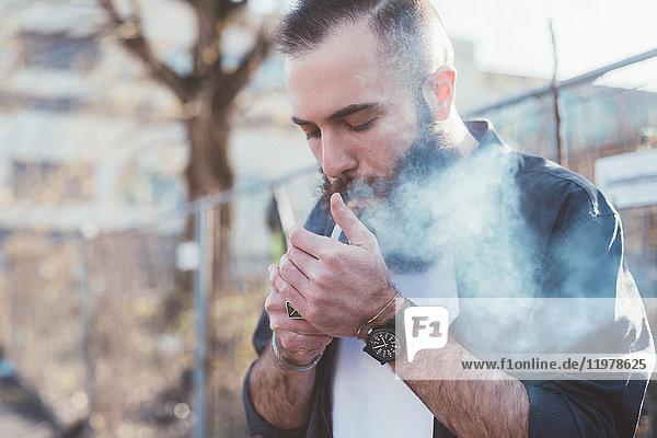Bärtiger Mann raucht eine Zigarette