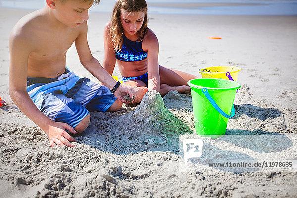 Geschwister spielen mit Sand am Strand