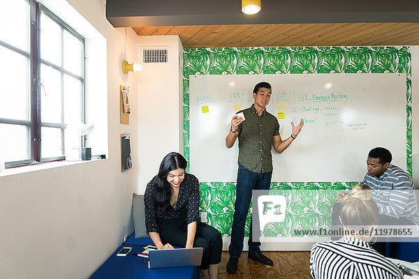 Junger Geschäftsmann präsentiert sich im kreativen Sitzungssaal