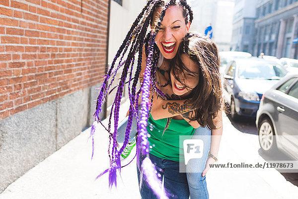 Frauen in Städtereise spielen Huckepack auf der Straße  Mailand  Italien