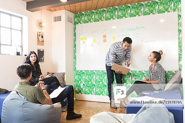 Junger Geschäftsmann betrachtet Laptop im kreativen Besprechungsraum