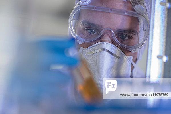Laborant  der ein mit Flüssigkeit gefülltes Reagenzglas hält  Nahaufnahme