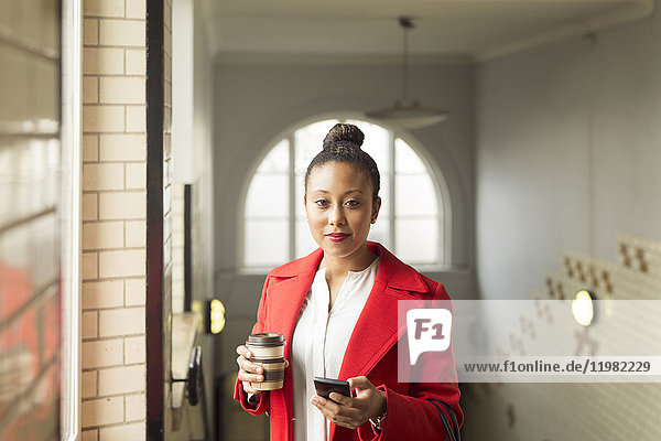 Portrait of woman in red coat holding coffee cup and smart phone