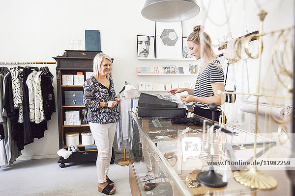 Woman standing by cash register