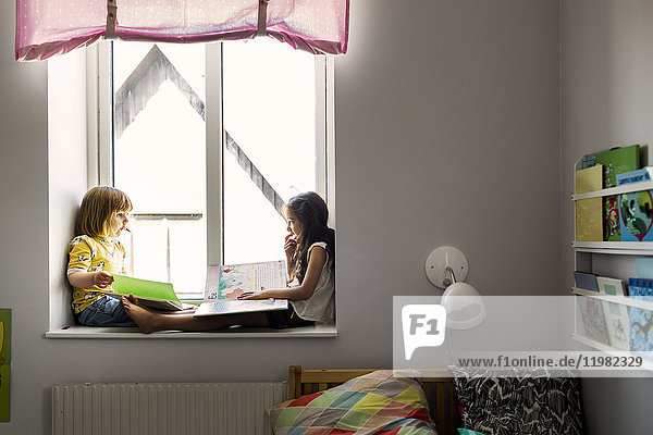 Girls (2-3  6-7) sitting and reading by window Girls (2-3, 6-7) sitting and reading by window