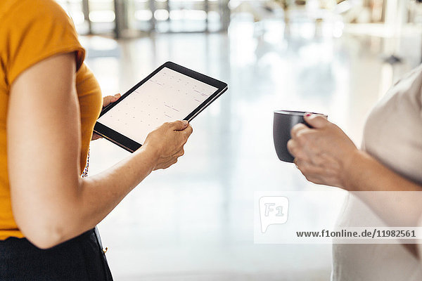 Mid section of two mature women  one holding digital tablet
