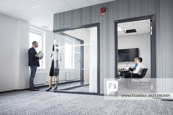Architects working in office and talking in corridor