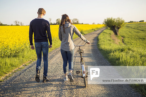 Young man and woman with bicycle walking on country road
