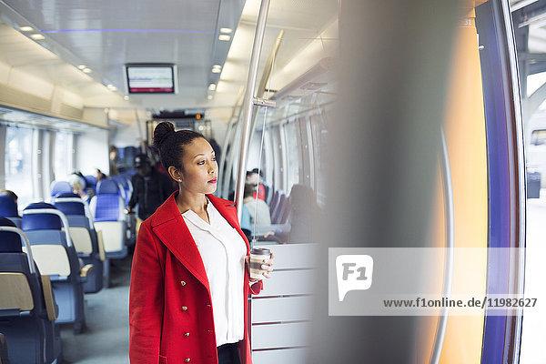 Woman in red coat looking through train window