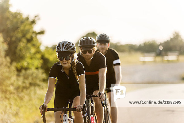 Three cyclists in rural setting Three cyclists in rural setting