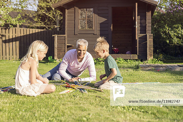 Father playing giant pick up sticks with daughter (8-9) and son (4-5) in garden