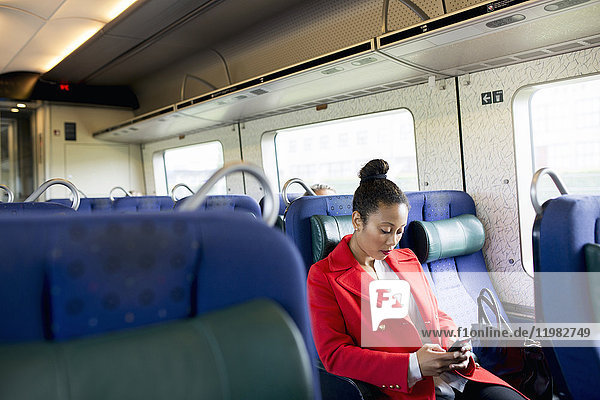 Woman in red coat sitting alone in train and using phone