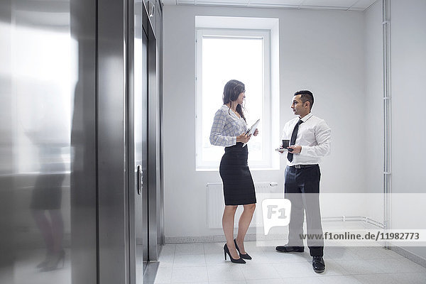 Businesswoman and man talking by elevator