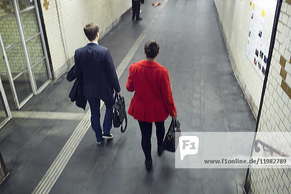 Rear view of man and woman walking at station