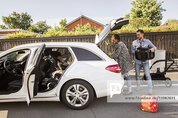 Son (18-23 months) sitting in car and parents packing luggage