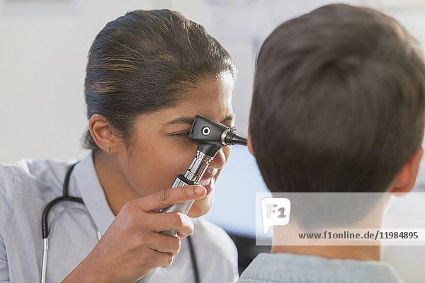 Female doctor using otoscope in ear of patient