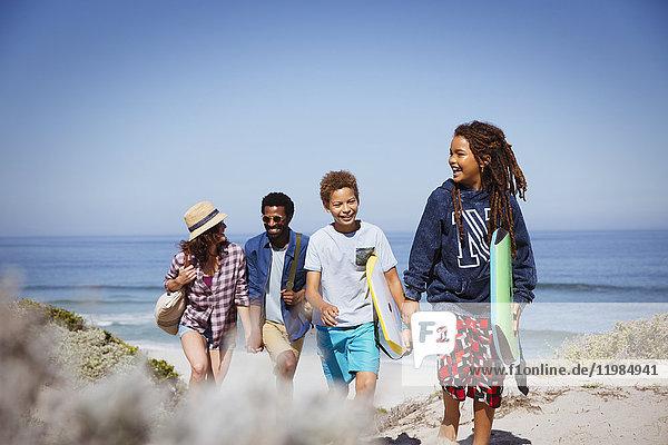 Multi-ethnische Familienwanderung mit Boogie-Boards am sonnigen Sommerstrand des Ozeans