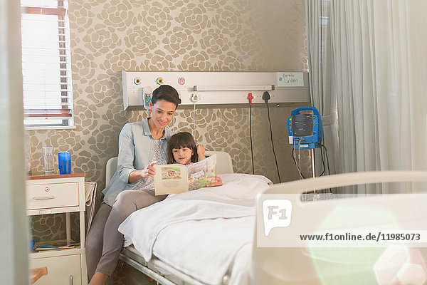 Mother reading book with girl daughter in hospital room