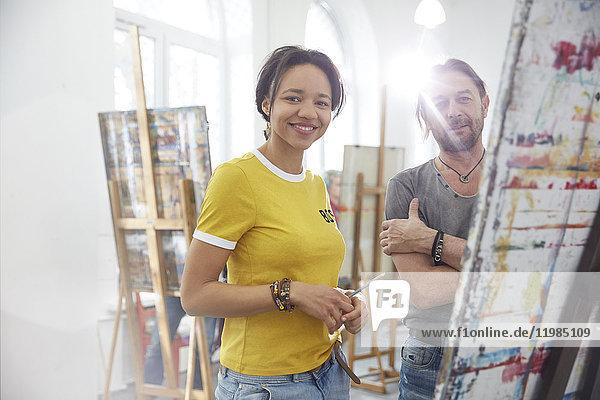 Portrait lächelnde Künstler malen an der Staffelei im Atelier der Kunstklasse