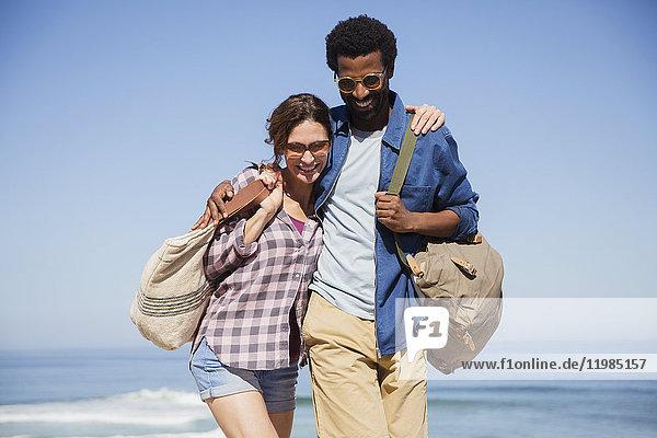 Lächelndes  liebevolles  multiethnisches Paar  das am sonnigen Sommerstrand spazieren geht.