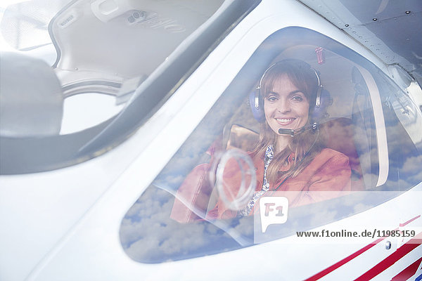 Portrait lächelnde Pilotin im Cockpit