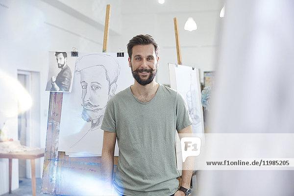 Porträt lächelnder  selbstbewusster Künstler beim Zeichnen im Atelier der Kunstklasse