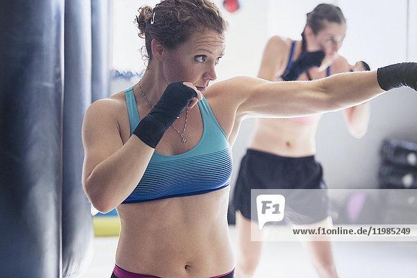Entschlossenes  zähes Boxerinnen-Schattenboxen im Fitnessstudio