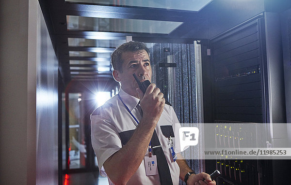 Männlicher Wachmann mit Walkie-Talkie im dunklen Serverraum