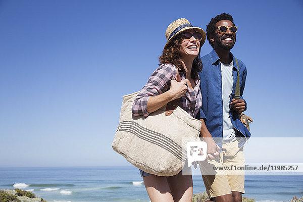 Lächelndes  anhängliches Paar  das sich an den sonnigen Sommerstrand hält