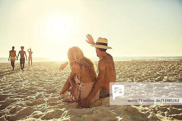 Junges Paar winkt Freunden am sonnigen Sommerstrand zu