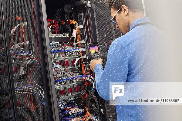 IT-Techniker  der die Diagnose am Panel im Serverraum durchführt
